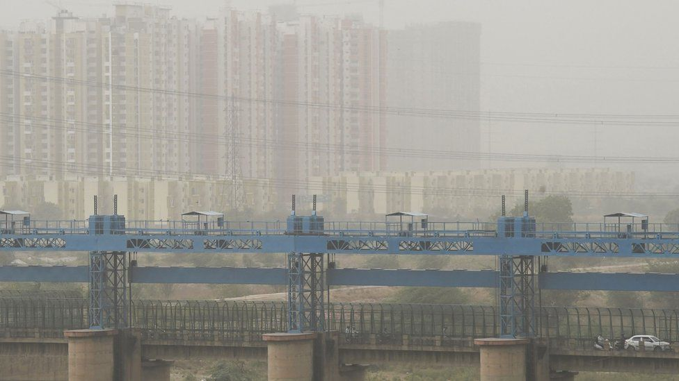 Vehicles cross a barrage on Hindon river as dust covers the skyline on the outskirts of New Delhi