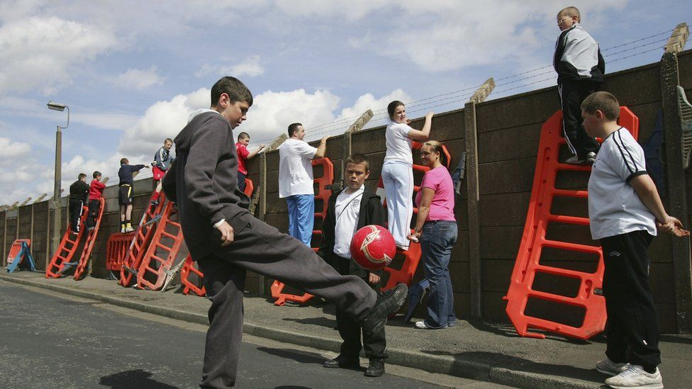 A young lad plays football as other Liverpool fans use roadworks barriers to get a glimpse of the Liverpool team training session ahead of the Champions League Semi Final Second Leg match against Chelsea at Melwood on May 2, 2005