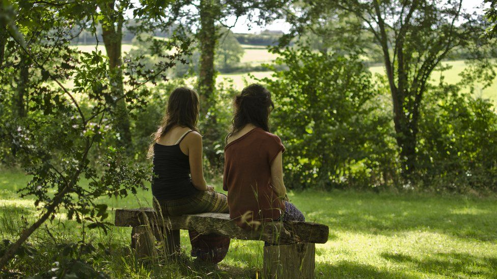 Two women sat on a bench outside during a silent retreat