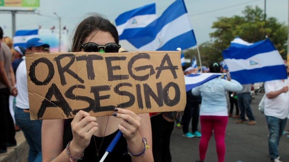 """A demonstrator holds a sign that reads """"Ortega Killer"""" during a protest march against Nicaraguan President Daniel Ortega's government in Managua, Nicaragua May 9, 2018."""