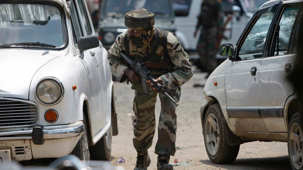 An Indian army soldier takes position during a fight in the town of Dinanagar, in the northern state of Punjab, India, Monday, July 27, 2015.