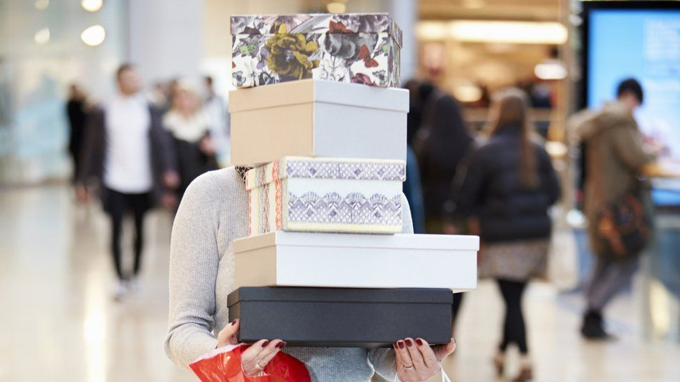 Carrying a stack of boxes and bags