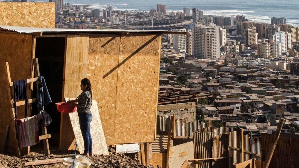 A woman stands outside her house at a camp in Altamira, Antofagasta, Chile, with the city of Antofagasta in the background, on 27 April