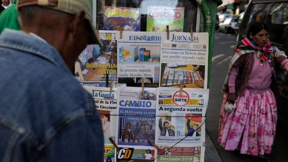 People read front pages of newspapers after the presidential election, in La Paz, Bolivia, on October 21, 201