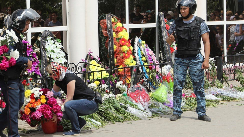 A woman places flowers as Interior Ministry members stand guard outside the firearms shop, which was a target of a recent suspected Islamist militant attack, during the funeral of salesman Andrey Maksimenko in Aktobe, Kazakhstan, June 8, 2016.