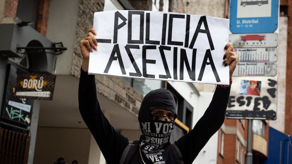 A demonstrator holds a banner that reads 'Killer Police' during a rally in Bogota, Colombia on August 26, 2021.