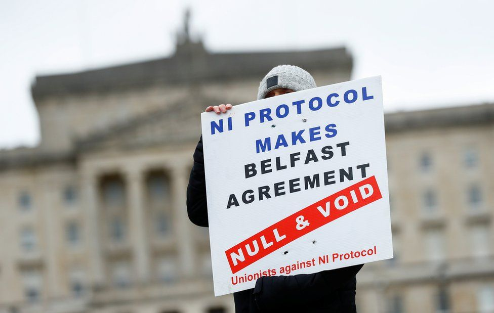 A loyalist protester at Stormont holds a sign that reads: NI Protocol makes Belfast Agreement null and void - unionists against NI Protocol