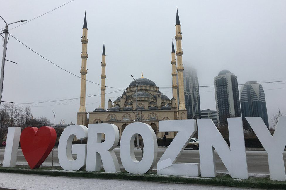 """A large street sign reads: """"I (heart symbol) Grozny, in front of a church, with skyscrapers seen in the background"""