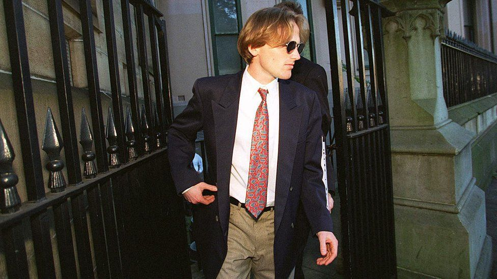 A man in a suit and sunglasses leaves court