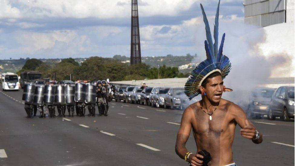 A member of an indigenous group stands before a group of riot police with shields during a land right protest in Brasilia on 25 April 2017