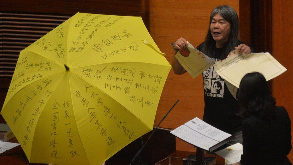 """Leung Kwok-hung - known as """"Long Hair"""" - of the League of Social Democrats shouts slogans and rips up the """"831 ruling"""" before taking the Legislative Council Oath"""