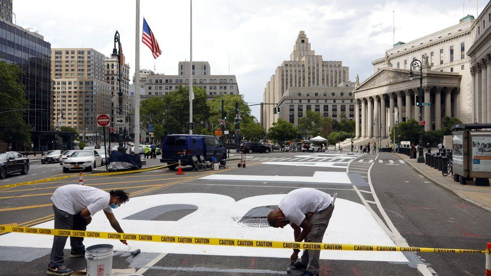 """Two men work on the recently painted giant letters spelling out """"Black Lives Matter"""" as seen in front of the Federal Court in Lower Manhattan in New York, USA, 01 July 2020"""