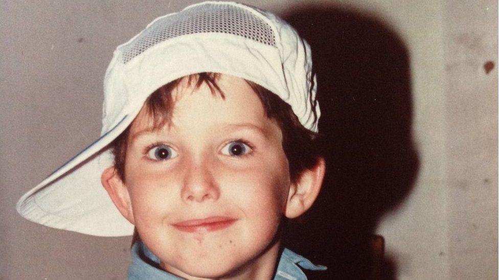 Young Jonathan Spollen in a baseball cap