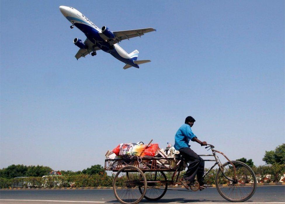 An IndiGo Airlines aircraft prepares to land as a man paddles his cycle rickshaw in Ahmedabad, India, October 26, 2015