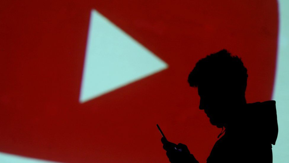 silhouette of a mobile user is seen next to a screen projection of YouTube logo in this picture illustration taken March 28, 2018