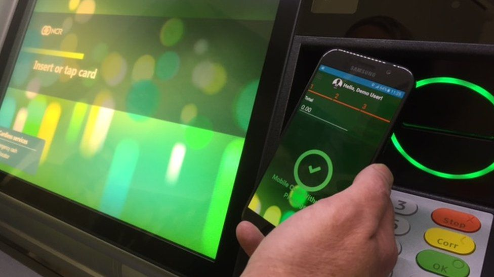 Person holding smartphone next to ATM
