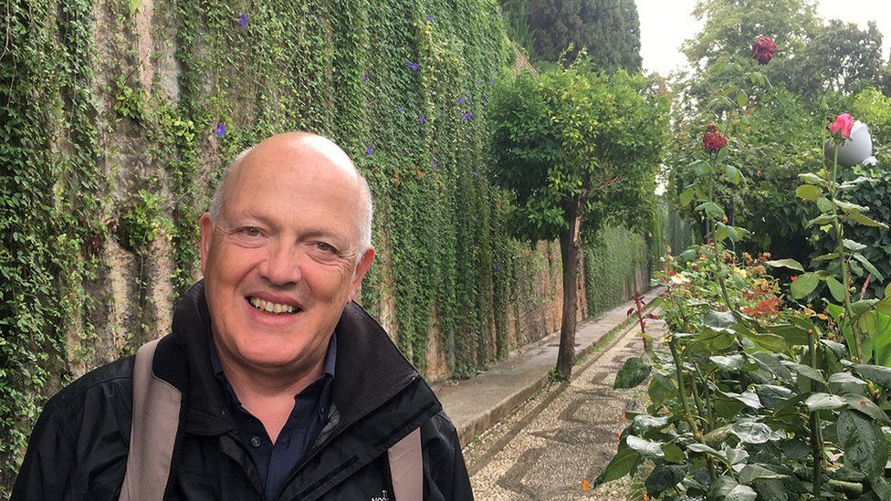 Klaus Vella Bardon is pictured in a manicured garden, with lush greenery stretching along the path behind him