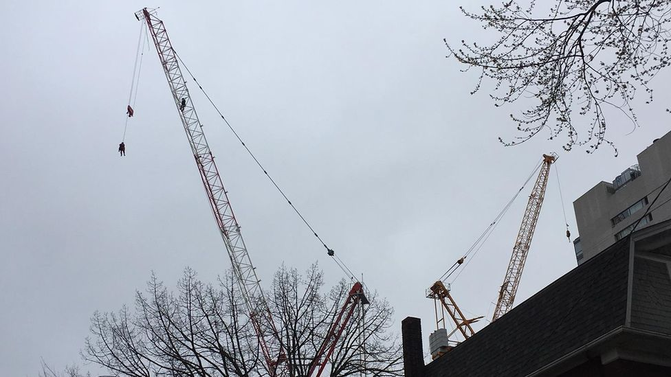 Rescuers bringing down the woman on the crane