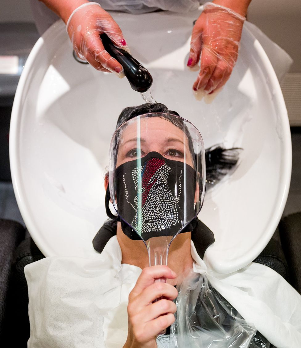 A customer wearing a face mask with David Bowie's face on has her hair washed in a hair salon
