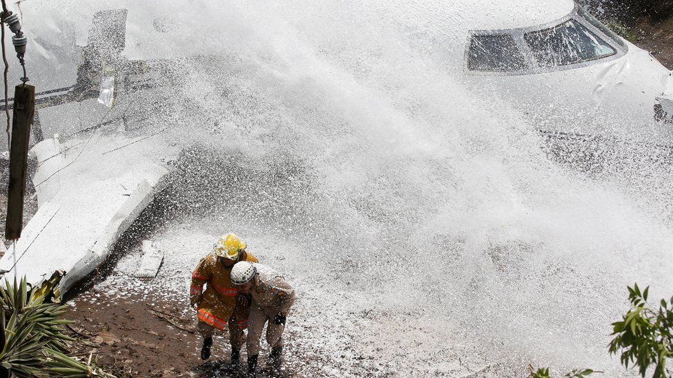 Firefighters take cover from firefighting foam applied onto the wreckage of a Gulfstream G200 aircraft that skidded off the runway during landing at Toncontin International Airport in Tegucigalpa, Honduras