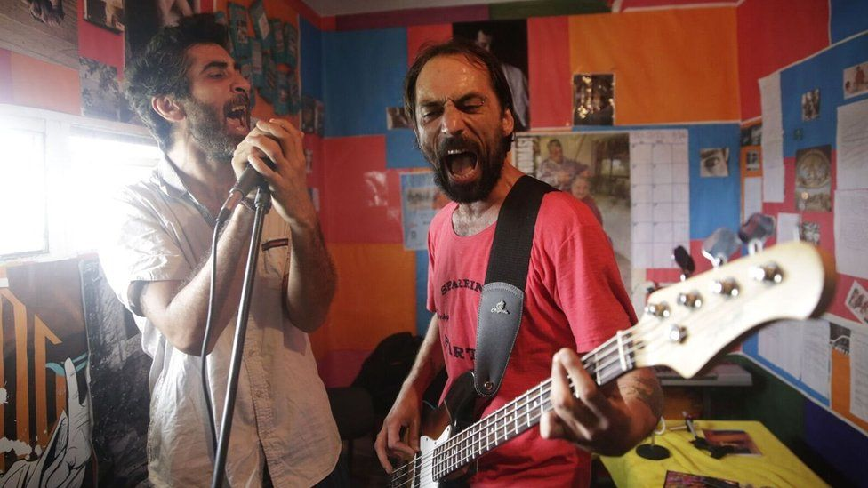 Two inmates sing and play the guitar in the music studio