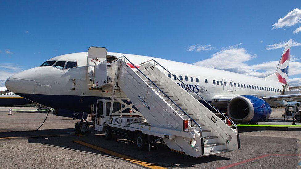 A British Airways plane with boarding steps beside it