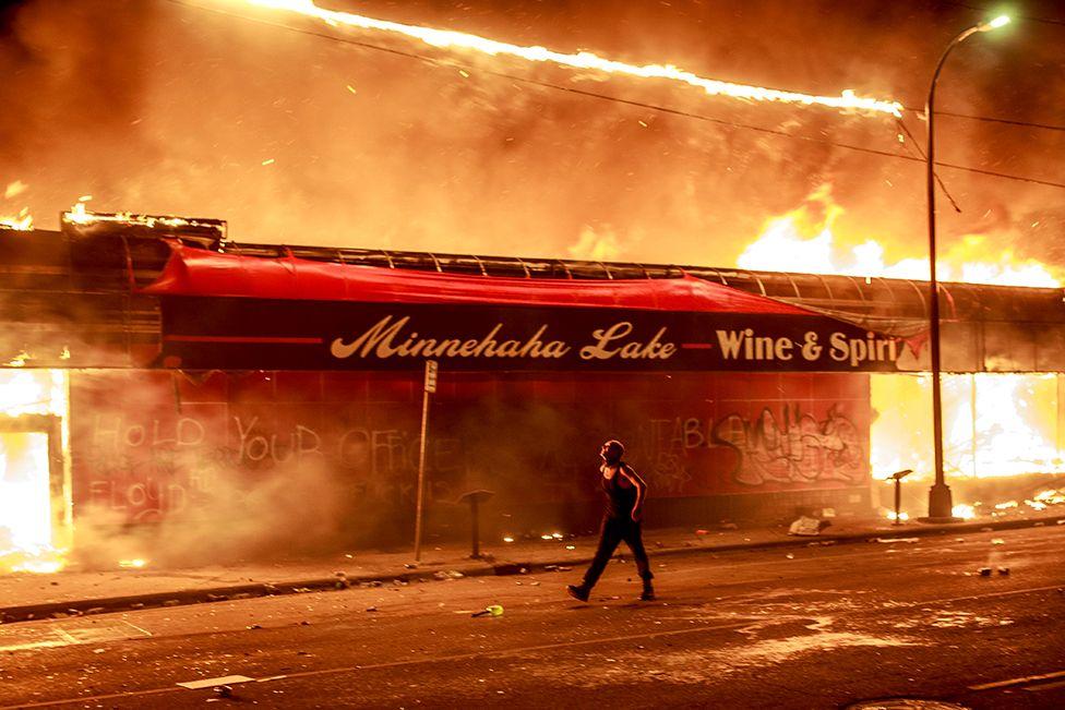 A man walks past a liquor store in flames