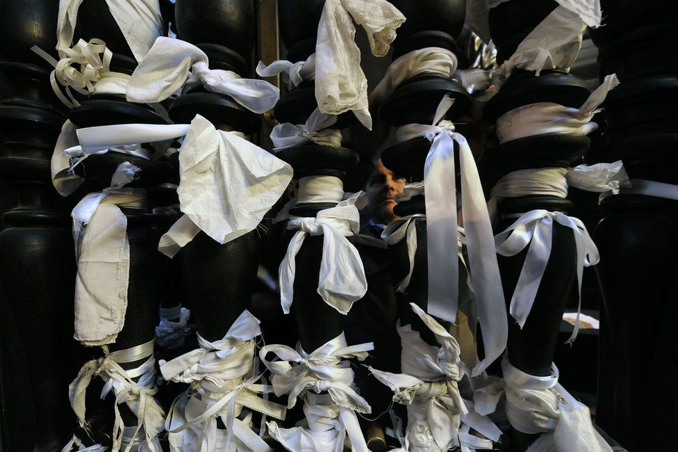 White ribbons tied to pillars on the gate of the San Gennaro chapel inside the cathedral of Naples, 5 March