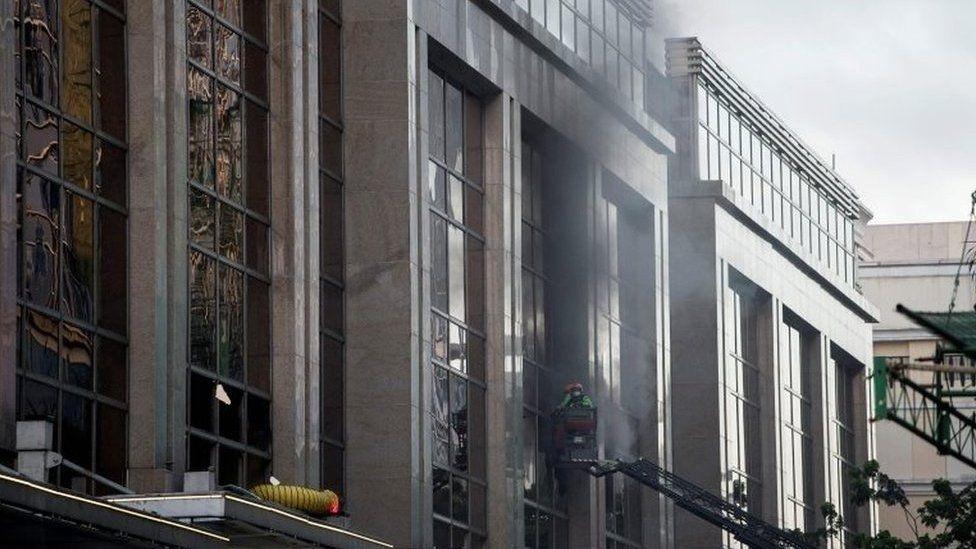 Firemen break a glass window of the Resorts World Hotel following an assault in Manila on 2 June 2017.