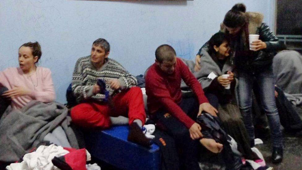 Survivors of Friday's boat sinking off Kalolimnos change clothes on Kalymnos, 22 Jan