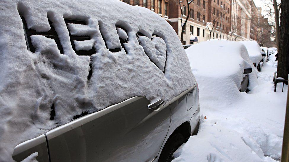 """""""help"""" written in snow on car"""