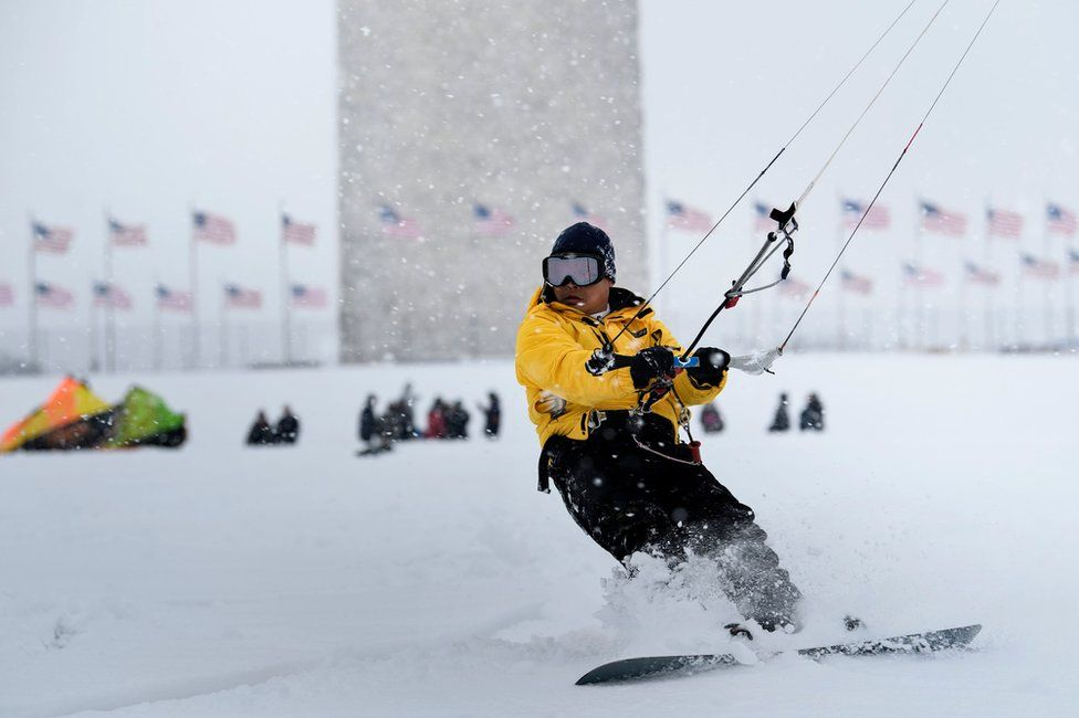 A man kite surfs in the snow