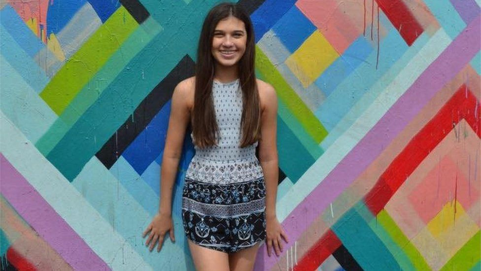 A teenage girl stands against a bright wall and smiles