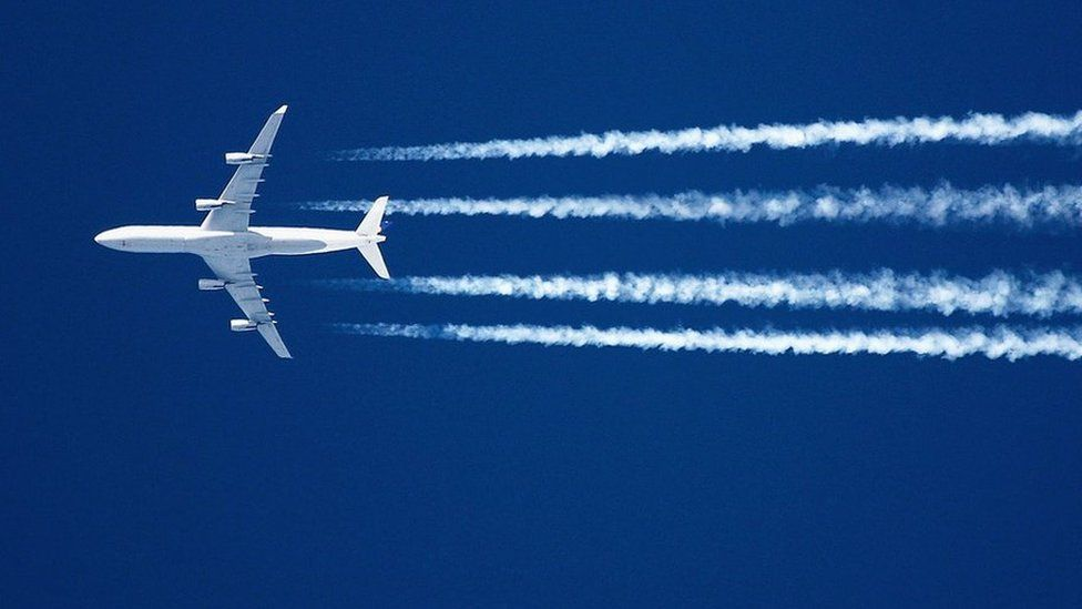 A plane flying in a blue sky