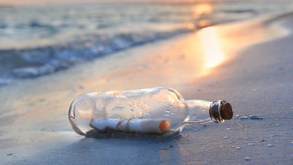 A bottle on a beach, with a note inside
