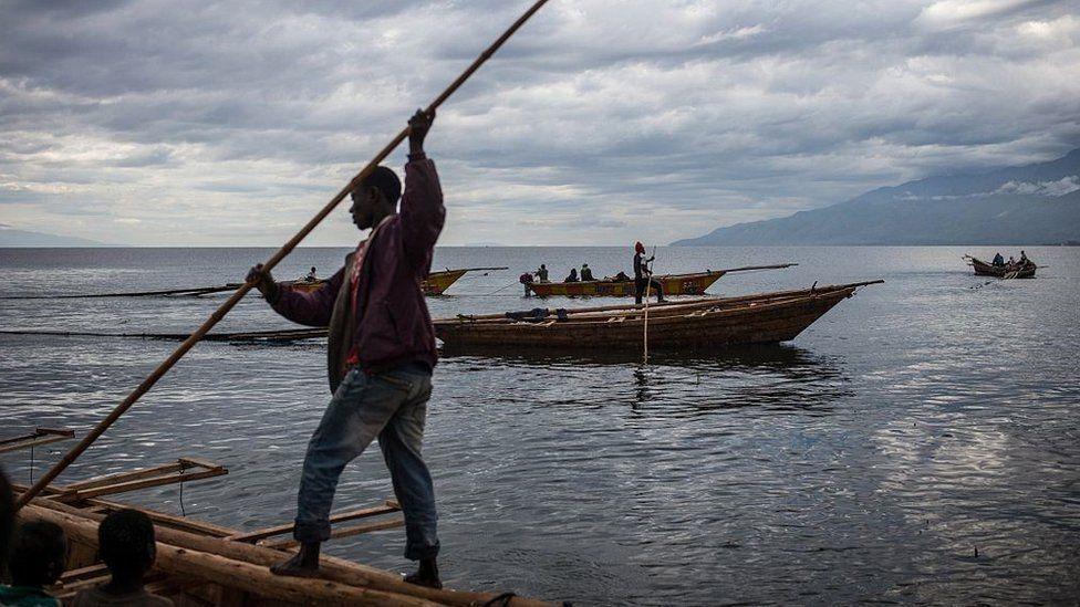 Fisherman manoeuvre to dock their boats on Tanganyika lake in Uvira on March 22, 2015