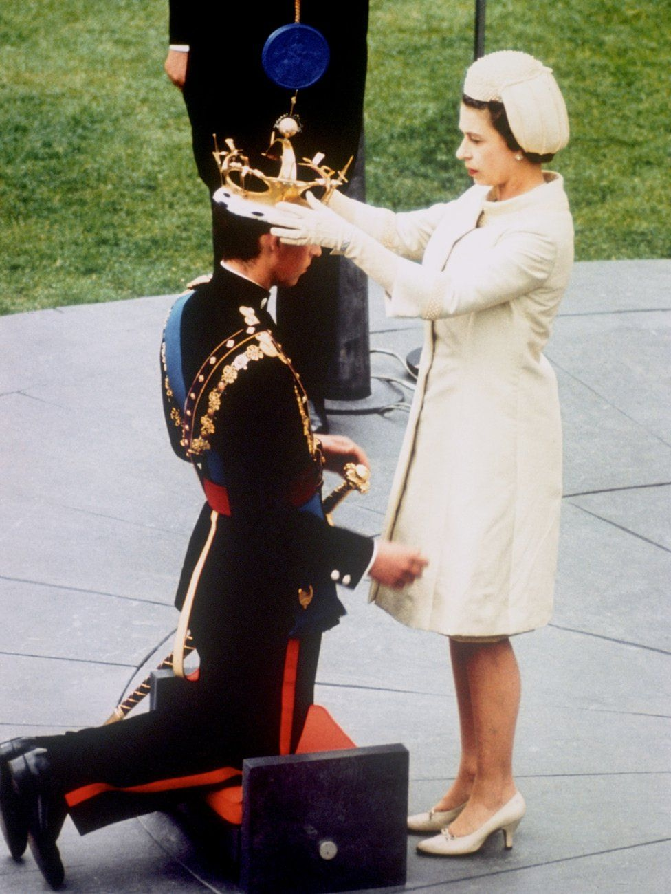 Queen Elizabeth II investing her son, Prince Charles