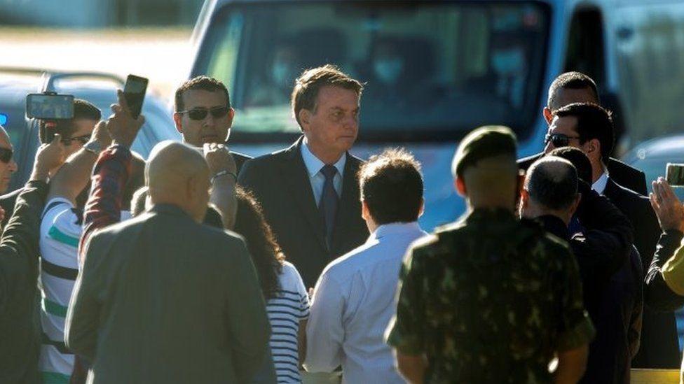 Brazilian President Jair Bolsonaro (C) leaves the Palacio do Alvorada, headquarters of the Presidency, in Brasilia, Brazil, 15 June 2020.