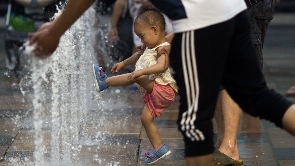 In this July 13, 2015 file photo, a child plays near water fountains at a shopping mall in Beijing