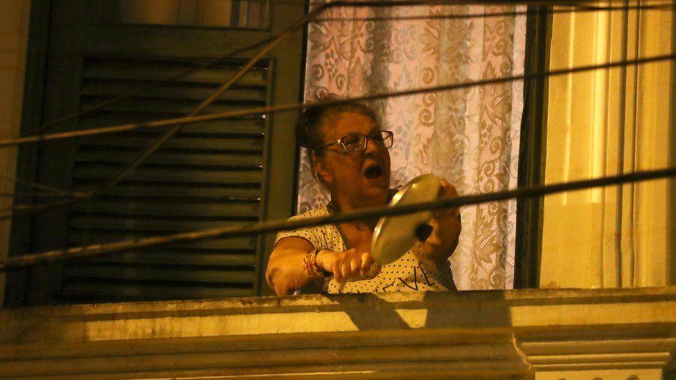 A woman in Rio de Janeiro beats a pot and pan during Jair Bolsonaro's speech