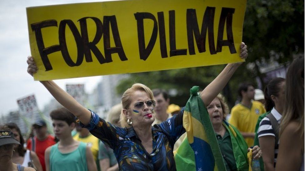 """In this Dec. 13, 2015 file photo, a woman holds a sign that reads in Portuguese; """"Dilma Out"""" during a demonstration in favour of the impeachment of Brazil's President Dilma Rousseff, on Copacabana beach in Rio de Janeiro, Brazil. J"""