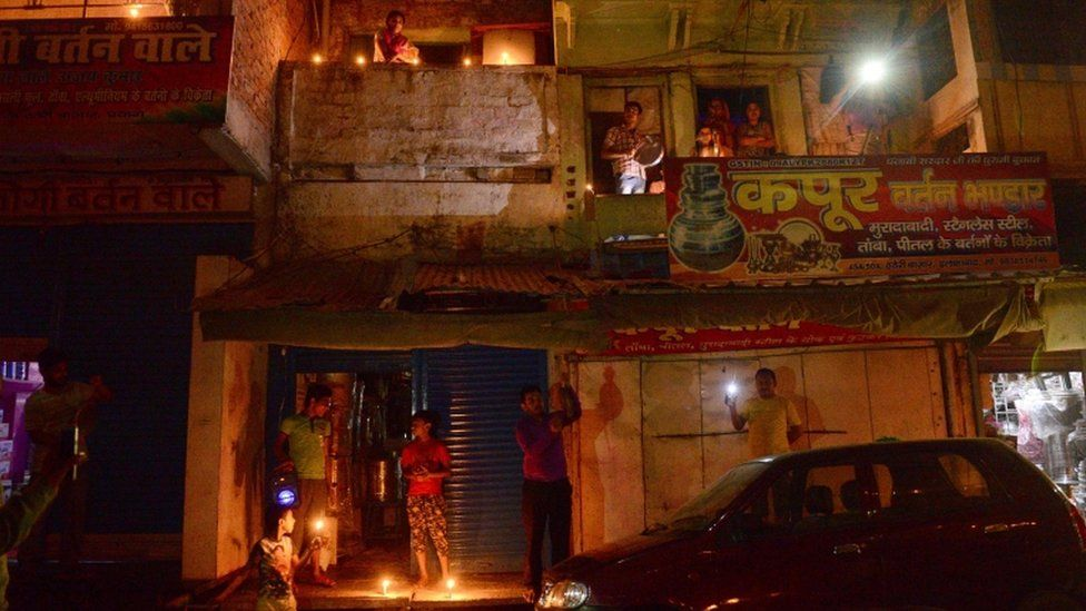 Residents light candles and turn on their mobile phone lights in India