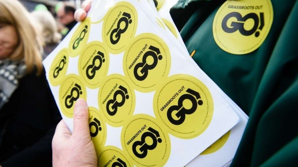 """An activist holds """"Grassroots Out"""" stickers in Wellingborough"""