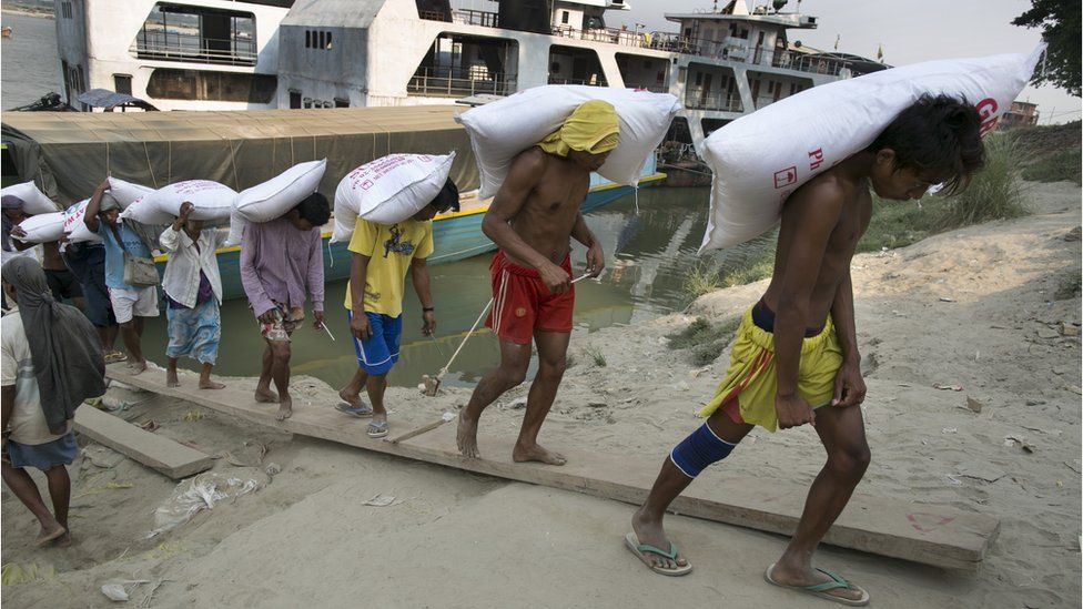 Workers carry a load off a boat on the Irawaddy River, Mandalay