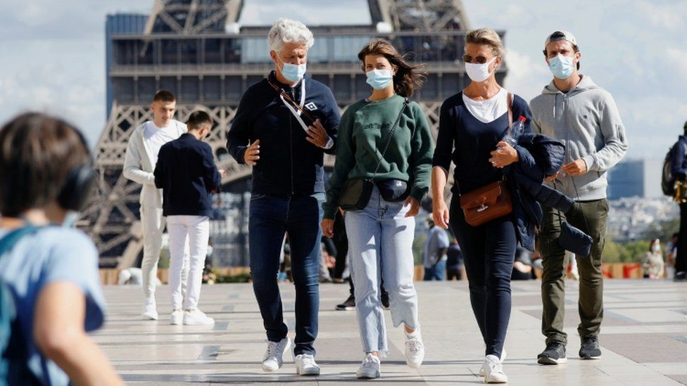 People wearing protective masks walk at the Trocadero square near the Eiffel Tower in Paris