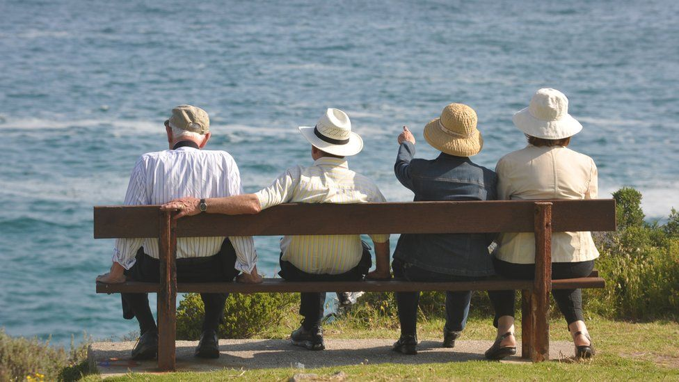 Two elderly couples sit on a bench and look out to sea