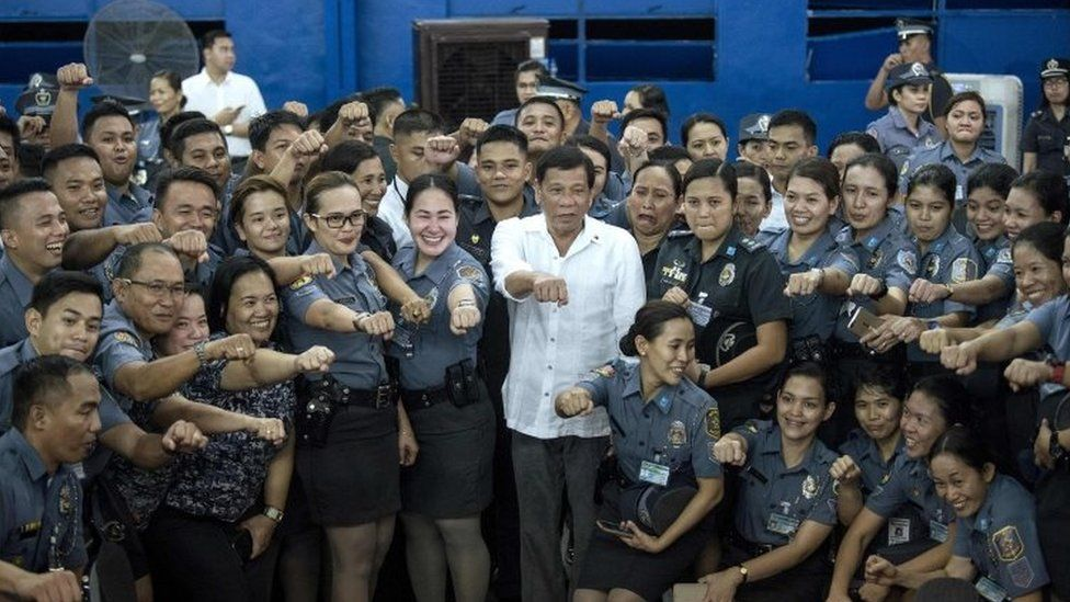 Philippines President Rodrigo Duterte (centre) poses for a picture with the Bureau of Jail and Penology Management (BJMP) personnel as he visits a detention cell of the BJMP located within Camp Bagong Diwa in Manila (19 October 2017)