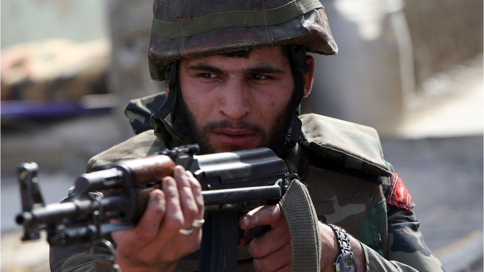 A Syrian army soldier aims his weapon during a battle against opposition fighters in the city of Qusayr