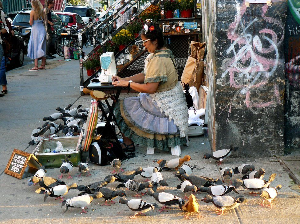 A woman using a sewing machine in a street, surrounded by model pigeons