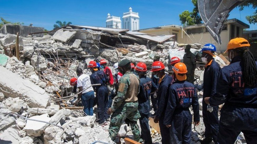 Members of a rescue and protection team clean debris from a house after a 7.2 magnitude earthquake in Les Cayes, Haiti August 15, 2021.